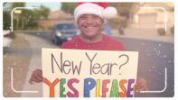 Young man in a Santa hat holding a sign that reads: New Year? Yes Please!