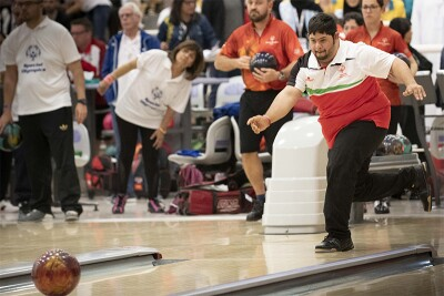 Saleh Al Marri in his lane, bowling as spectators watch in the background.