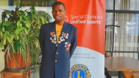 Nyasha Derera standing infront of a Special Olympics Unified Sports banner in a blue sports coats and yellow special olympics shirt.