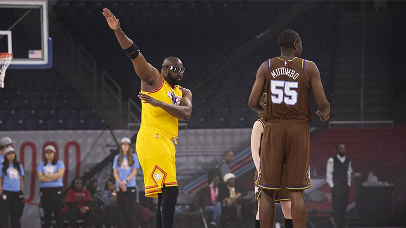 Three players on the court. The player in yellow is giving hand signals.