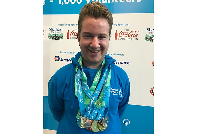 Shane Baxter smiling with a collection of medals hanging around his neck.