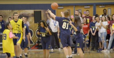 Zack shooting the basketball at the last second of the game with teammates watching.
