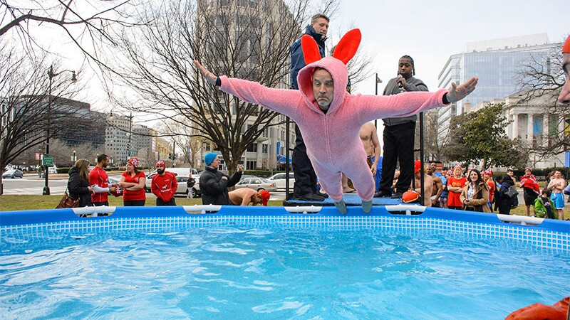 May in a rabbit suite jumping into a pool of water as spectators watch.