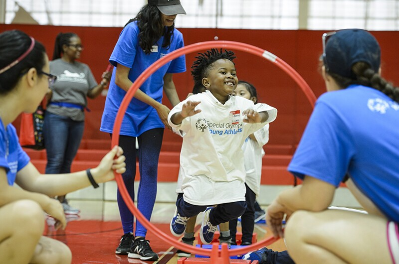 A young athlete smiles as he jumps through a hoop that is being held by two volunteers.