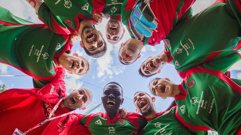Footballers form the Special Olympics Italia team standing in a circle looking down at the camera and the camera shooting the photo looking up; the sky is in the background.
