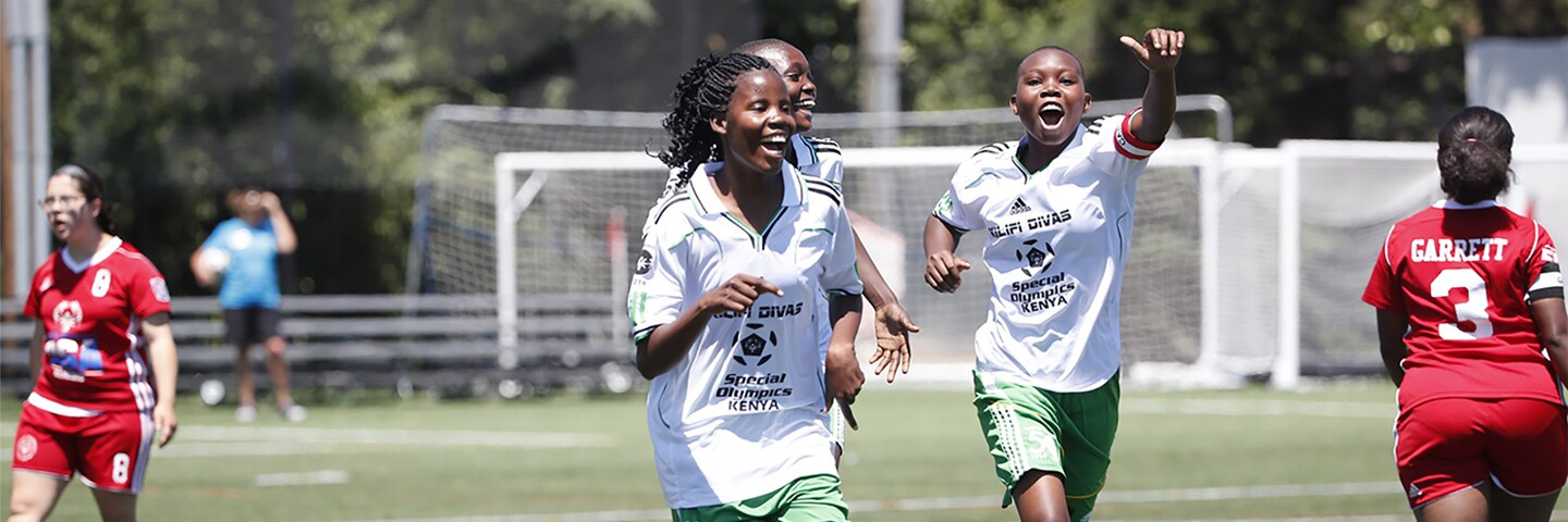 Three girls in white and green on the pitch celebrating and two girls in red.
