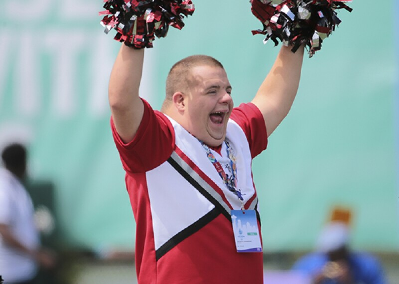 Special Olympics athlete cheerleader showing his support with his palm-palms up in the air and team spirit on his face.