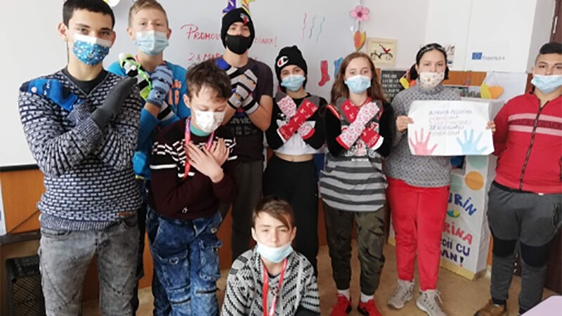 Approximately 10 school students, wearing facemasks, pose together making the same crossed-arm motion inside a classroom. One student holds up a drawing with hands on it.