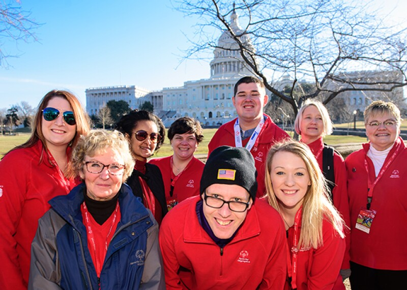 A group of athletes and Special Olympics representatives standing in front of the Capitol building.