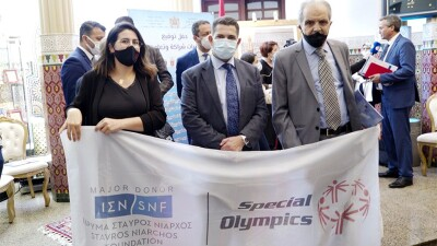 One woman and two men, masked and dressed professionally, hold a banner with the Stavros Niarchos Foundation and Special Olympics logos on it.