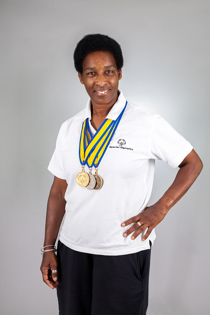 Loretta stands and poses for a photo with three medals displayed proudly around her neck.