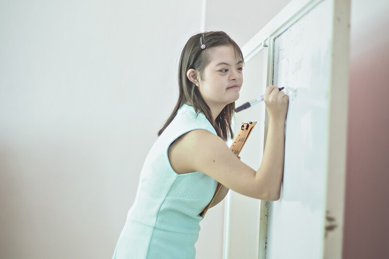 Briana writes on a white board while working as an assistant teacher.