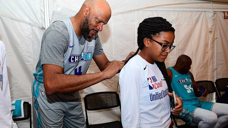 Five-time NBA champion Ron Harper signs the jersey of Special Olympics Florida, USA athlete Janaiya Warren. a player is sitting on a chair in the background.