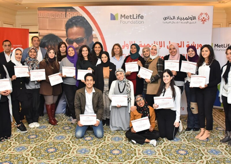 A group of 20 athletes siblings stand together in a group photo holding their certificates after completing the Siblings Workshop.