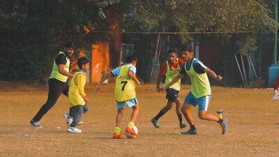 A group of young athletes playing football in a field.