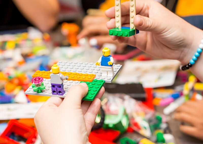 "Group of people sitting around a table working with ""Lego"" type blocks."