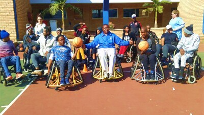 Ephraim experiencing sitting in a wheel chair surrounded by para-olympians. An athlete on either side of him is holding a basketball.