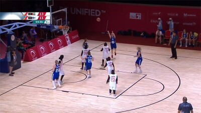 Arial shot of female player shooting for the hoop; 9 other players accompany her on the court along with three officials and spectators can be seen int he background.