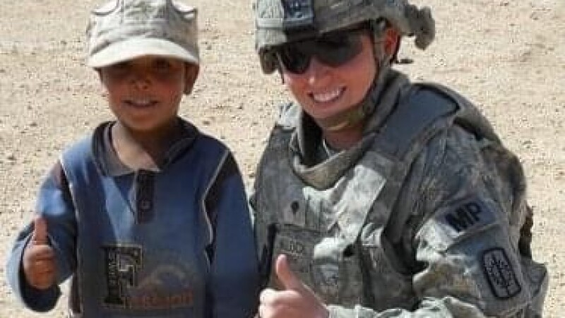 Monica Klock in Iraq giving a thumbs up with a young child