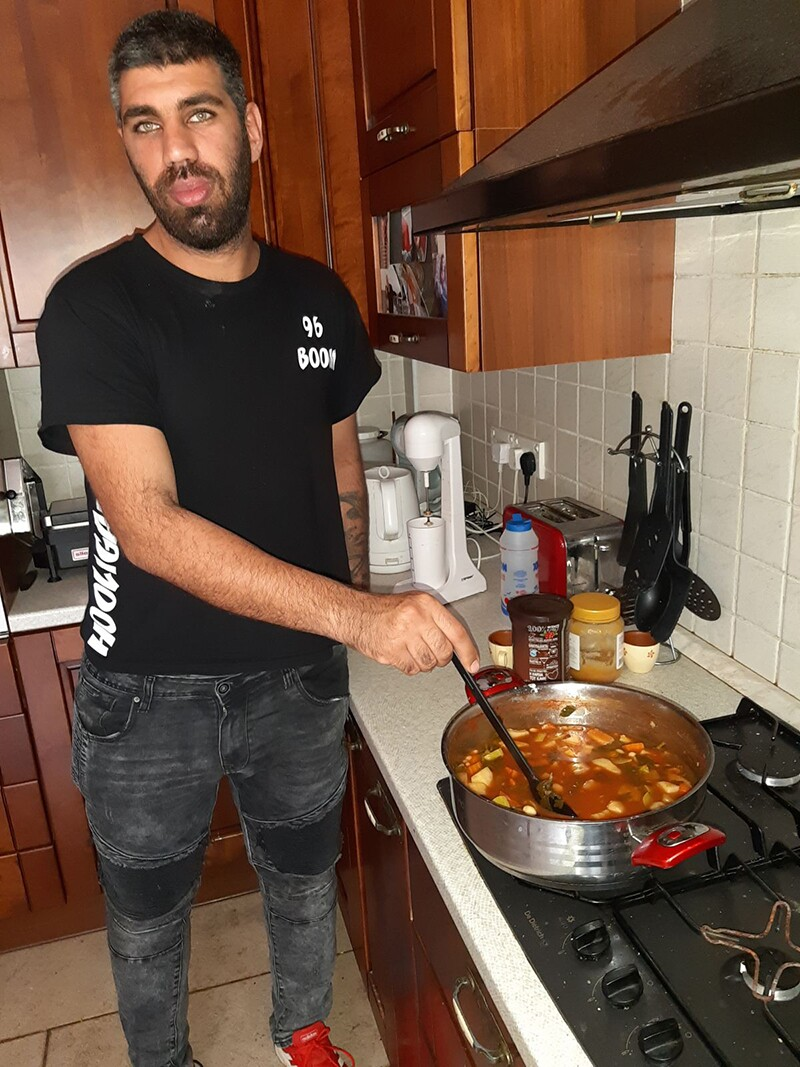 Athlete in the kitchen at the stove stirring slow cooked beans.