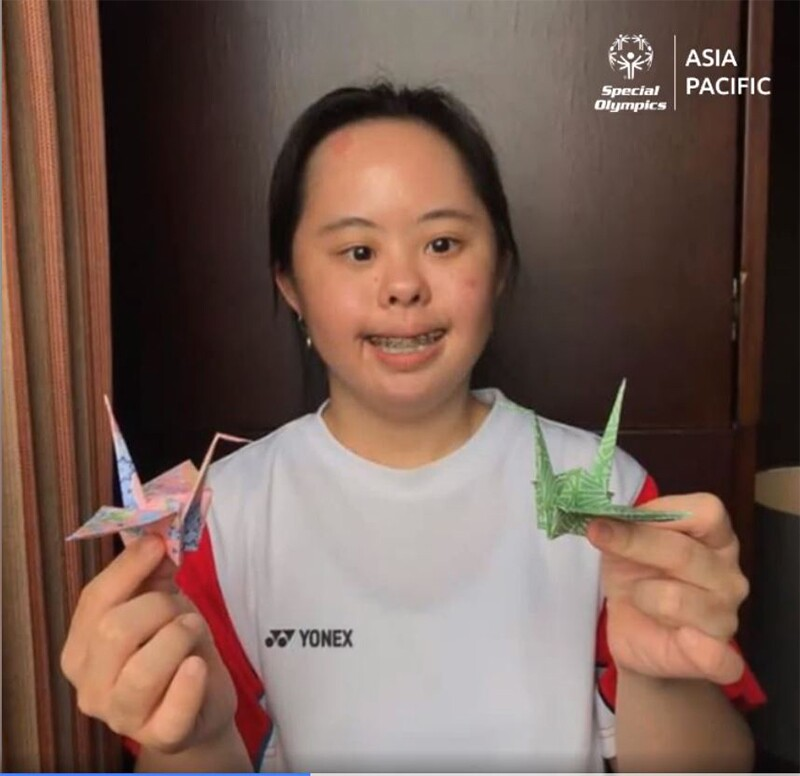 Stephanie holding two paper cranes.