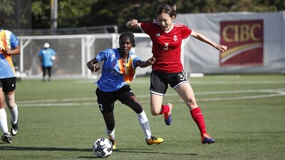 Two female footballers on the pitch trying to take control of the ball.