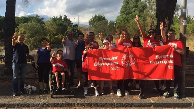 A group of walkers outside holding a Special Olympics Italia banner.
