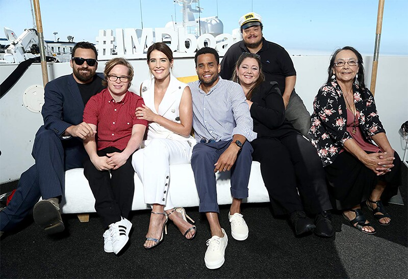 The cast of Stumptown sitting together in a group on a white couch.