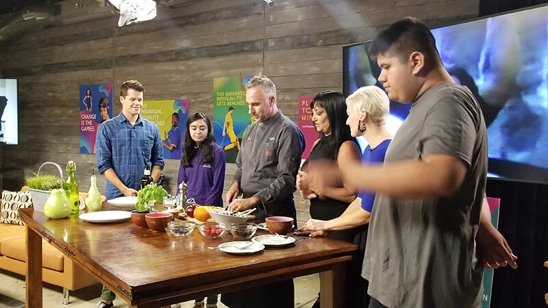 Six people on a set standing around a table with food.