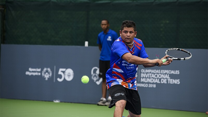Male athlete tennis player on the court taking a swing at the ball.