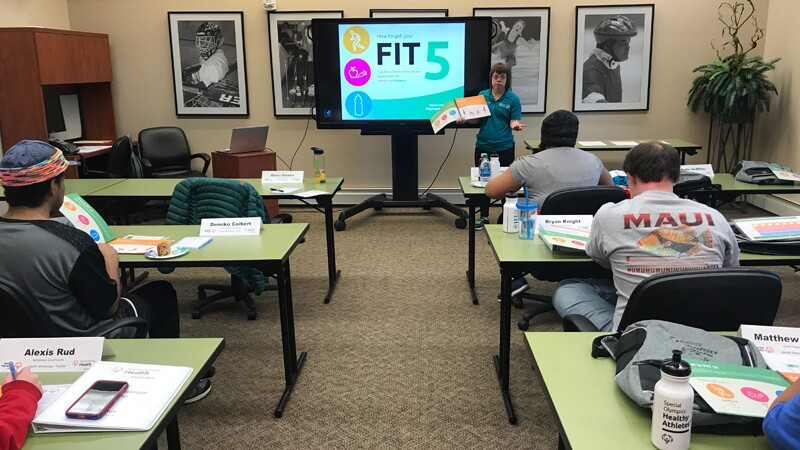 An instructor at the front of the room teaching content related to Fitness as students pay attention.