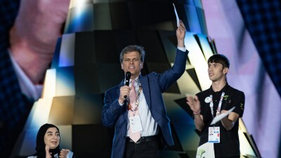 Timothy Shriver on stage during the 2019 closing ceremonies giving a speech. A young man standing and applauding on the right and a woman sitting and applauding on the left.