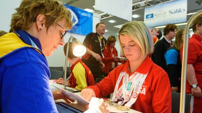 Daina Shilts sitting at a desk with her medals around her neck reading over a card with a health representative.