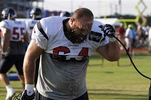 Houston Texans offensive lineman, Kasey Studdard, hoses himself down during a hot practice.