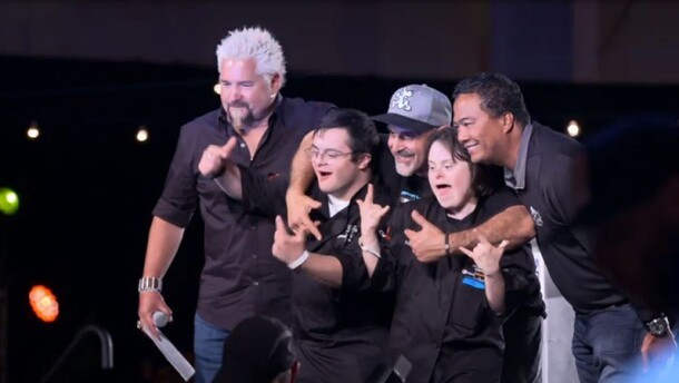 Guy Fieri on stage with athletes.