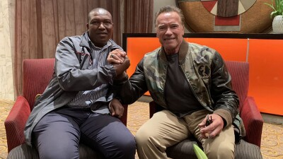Arnold Schwarzenegger and Ephraim Mohlakane sitting next to one another in chairs shaking hands.