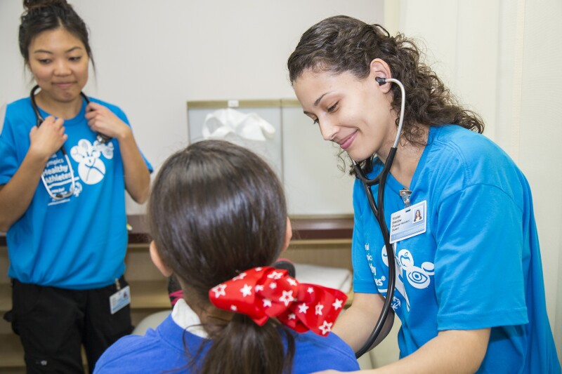 A health professional leans in to listen to a young girl's heart through a stethoscope.