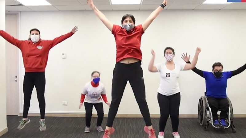 Five youth perform a jumping jack, with arms outstretched in the air. They are all different heights and abilities, one has a wheelchair. They all wear masks and Special Olympics shirts.
