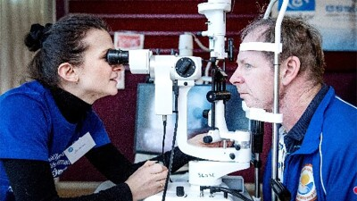 A male athlete has his eyes examined by a female healthcare worker. His head is in a harness allowing her to look through the microscope at his eyes.