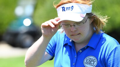 Close up of Amy adjusting her sun visor that has her name on it.