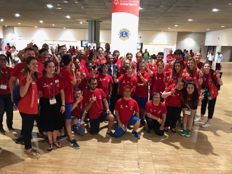 A large group of young people in red t-shirts face the camera smiling with their hands in the air. They are in a large indoor hall with a Lions Clubs International pull-up banner in the background.