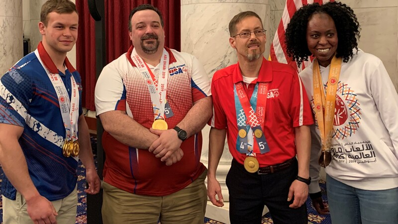 Four people stand and smile in front of the U.S. flag. They are all wearing medals and Special Olympics clothes.