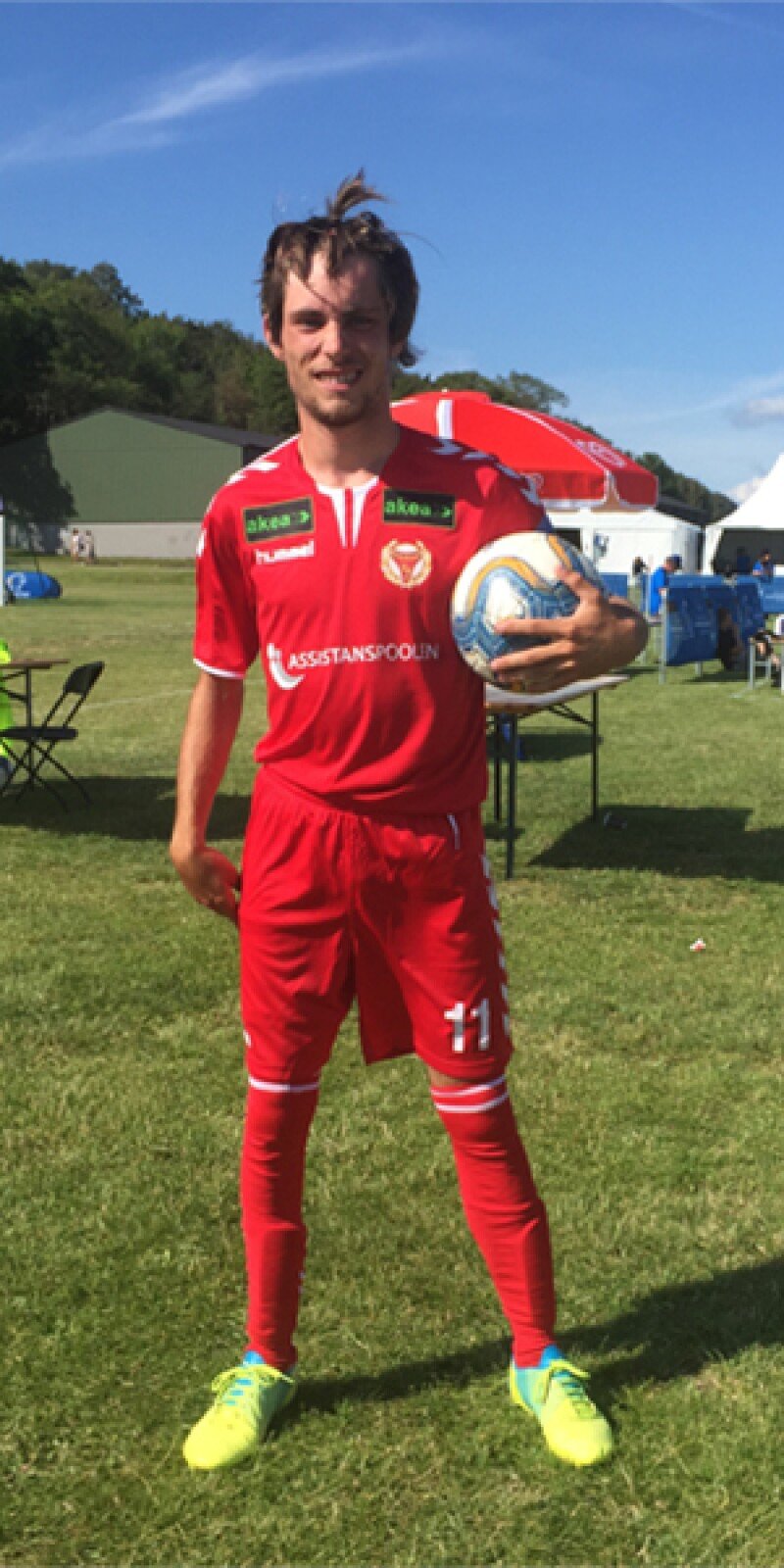 A man stands in a red football kit holding a football and facing the camera at the sidelines of a football pitch.