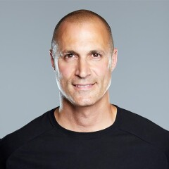 Nigel Barker in a black t-shirt smiling for his headshot.