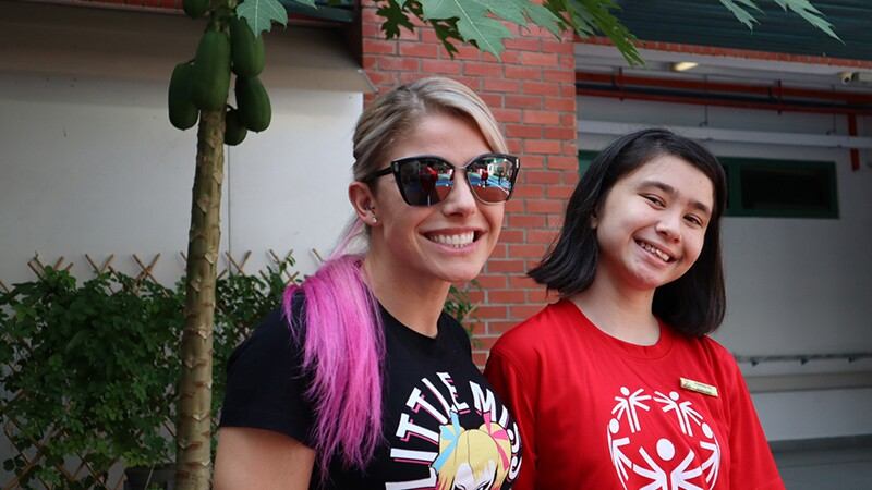 Young girl with blond and pink hair has on sunglasses and stands next to an athlete with short black hair in a red Special Olympics shirt, stand side by side smiling.