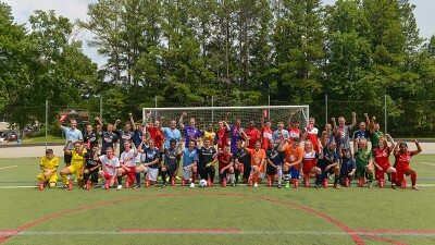 Soccer players (footballers) in two rows (front row keeled down and back row standing) from all different unified teams outside in front of the keepers net in a group photo.