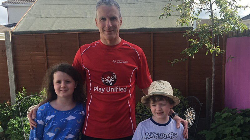 Will Byrne with his two daughters in the back yard after a run.