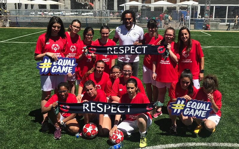 A man stands in the middle of a group of girls in red Special Olympics t-shirts holding signs saying '#EqualGame' and #Respect on a football pitch.