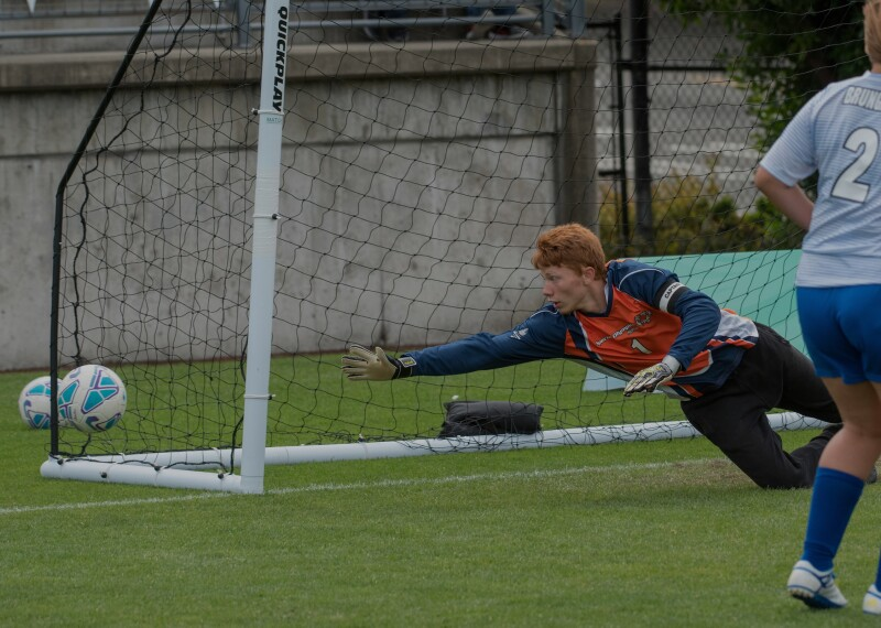 keeper diving for the ball before it makes it into the net.