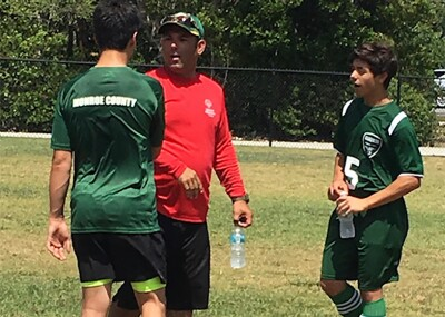 Coach Pedro with two athletes on the field.